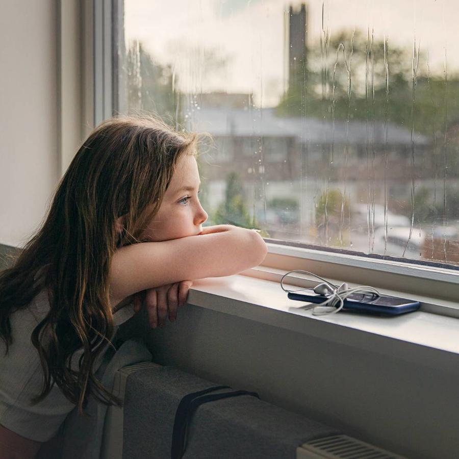 Niña mirando por la ventana