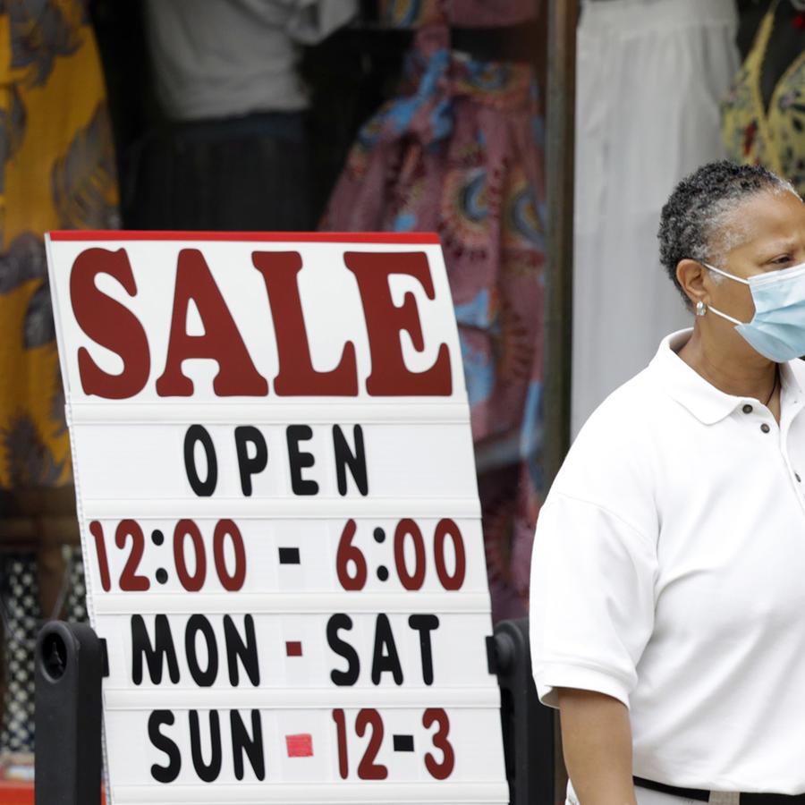 Una mujer frente a una tienda con ofertas en Cleveland Heights, Ohio.