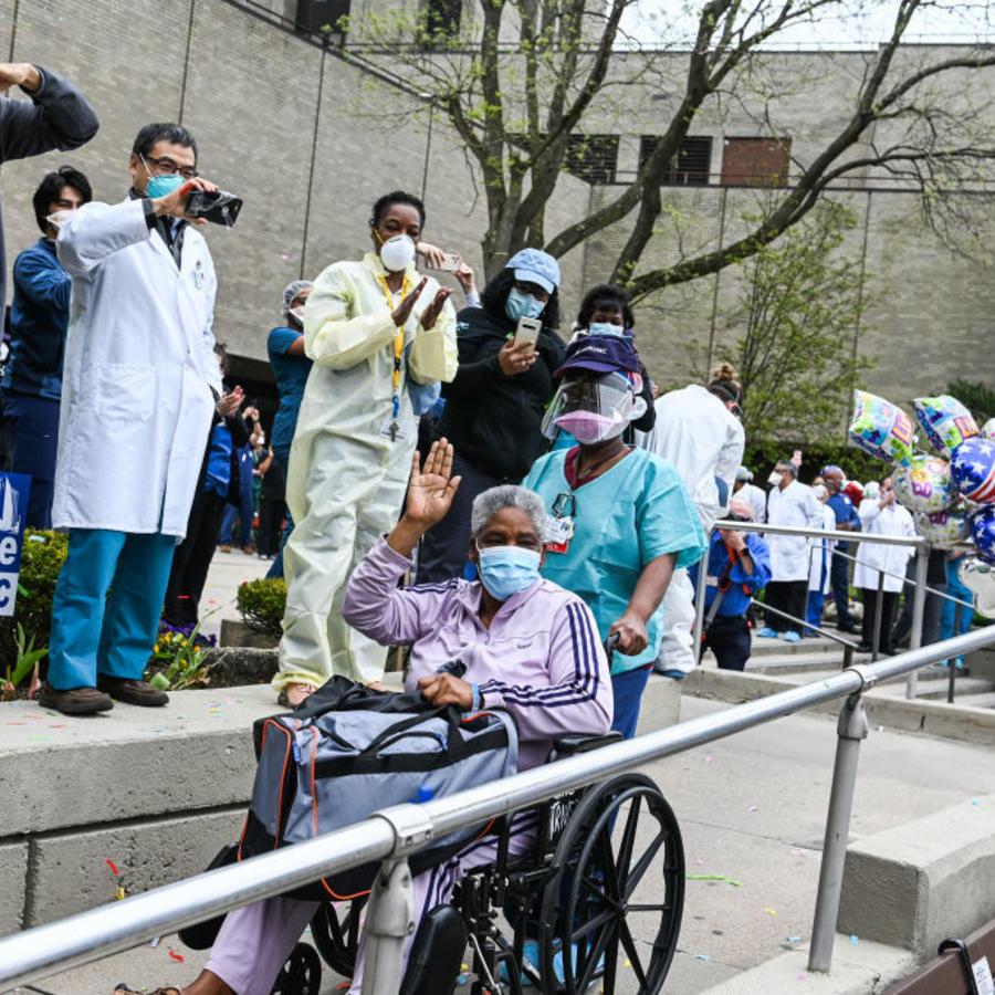 Trabajadores de la salud celebran el alta de una paciente recuperada de COVID-19 en Nueva York.