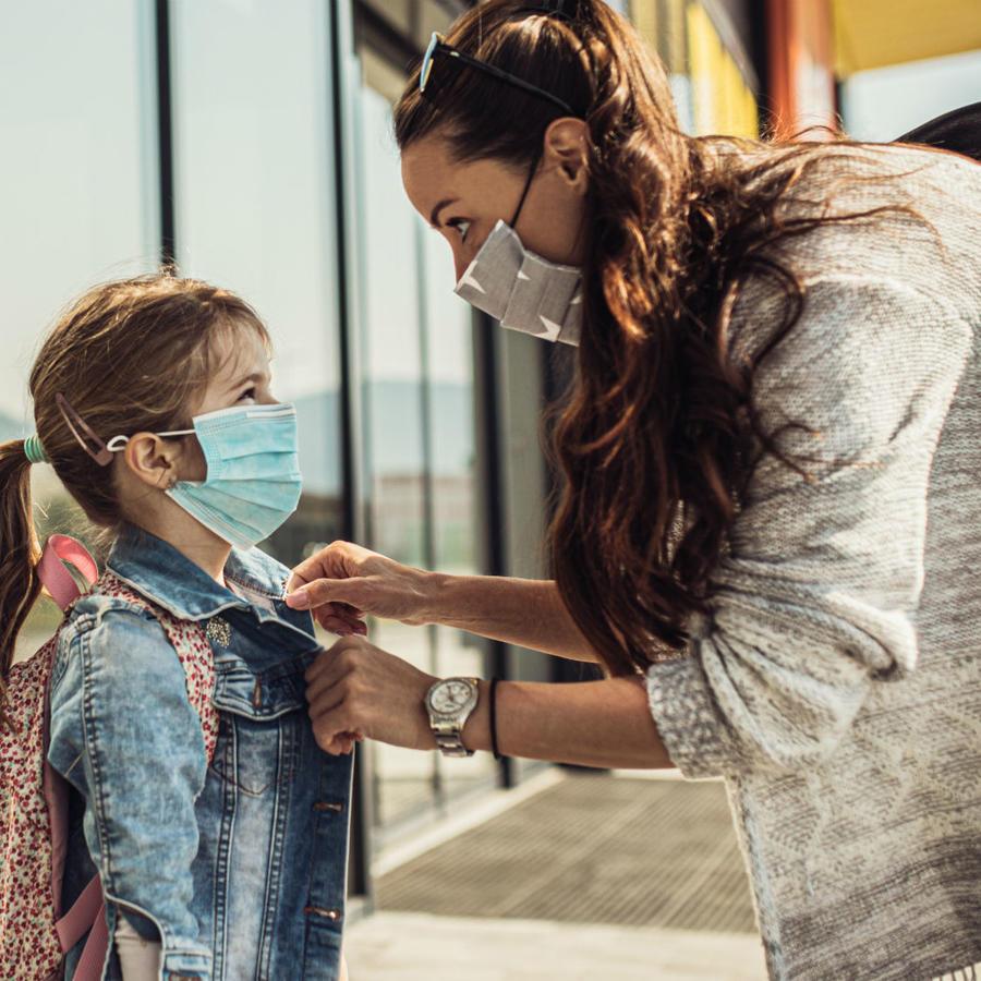 Mujer preparando a su hija para la escuela
