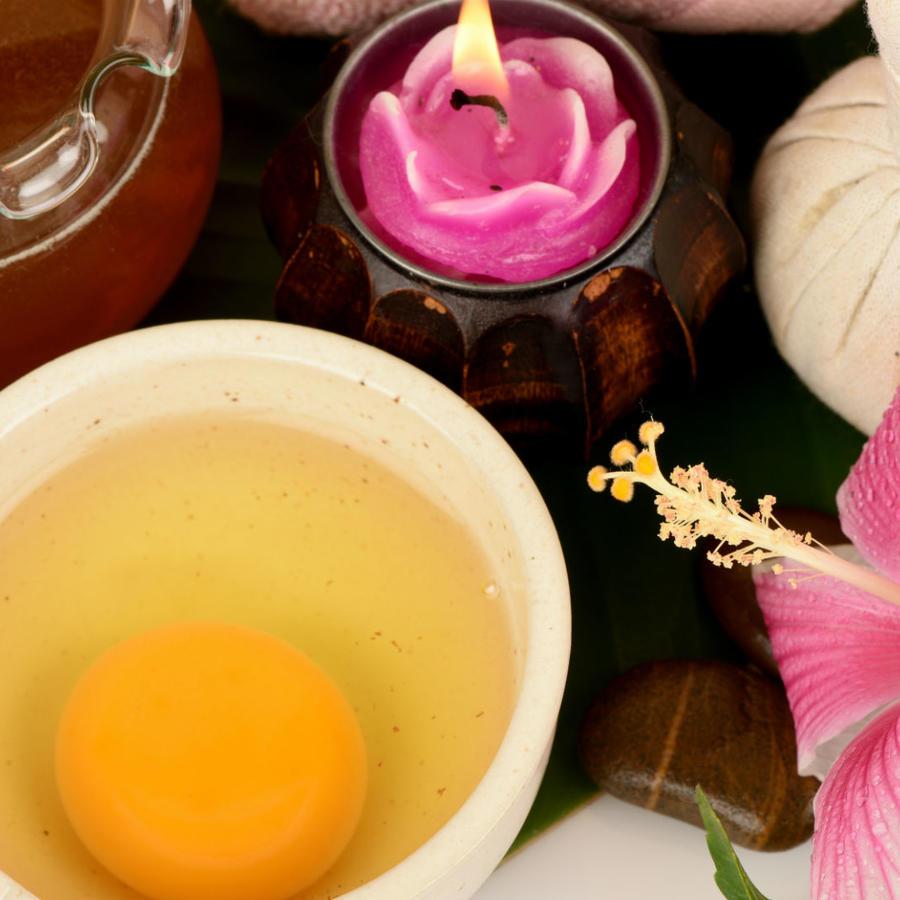 Yema y clara de huevo en un bol blanco, junto a miel, flores y una vela