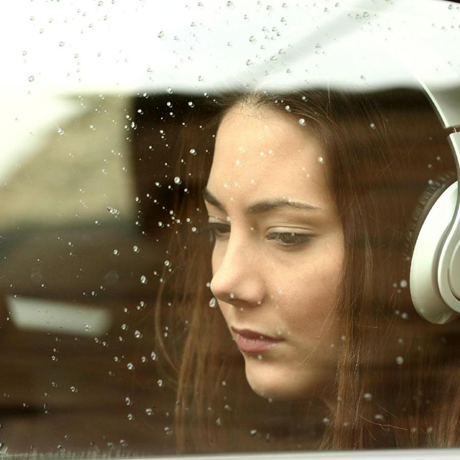 Mirando triste por la ventana del auto