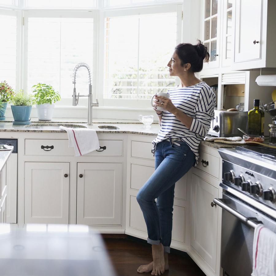Mujer pensativa en la cocina bebiendo café
