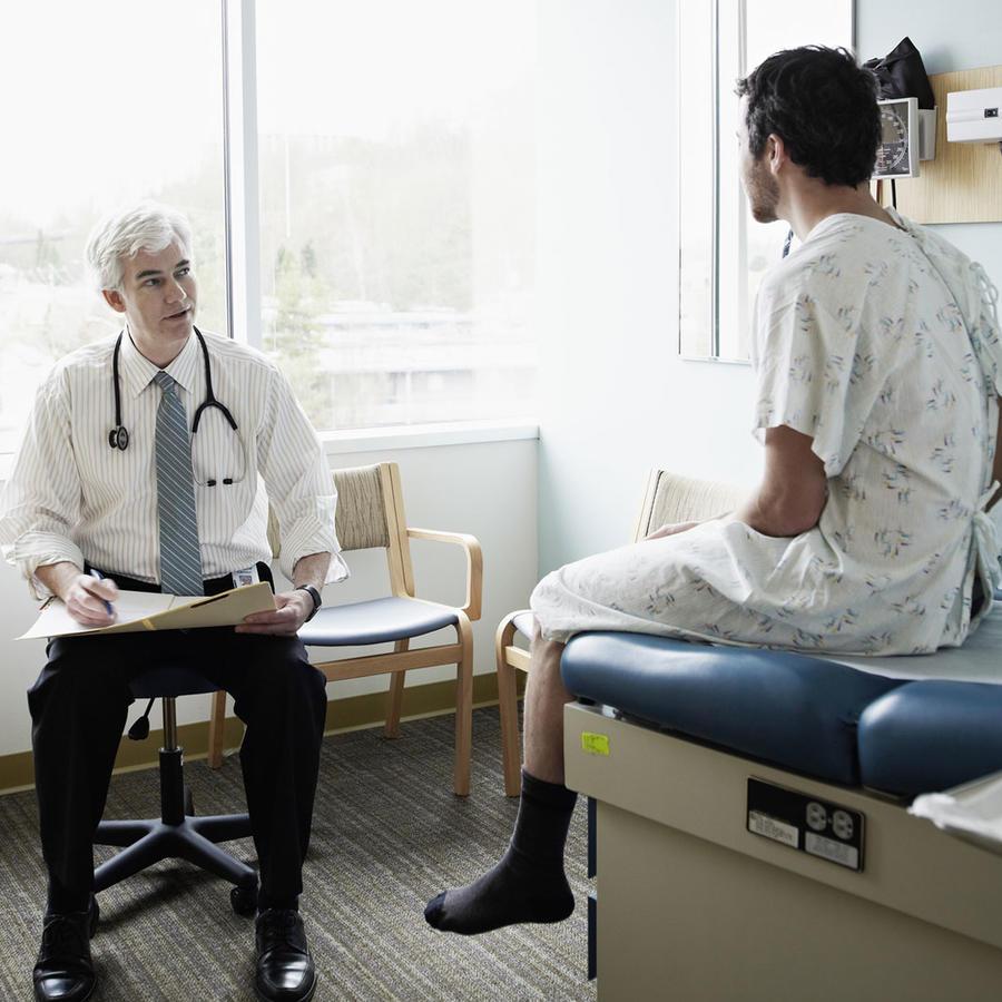 Paciente en bata hablando con un médico