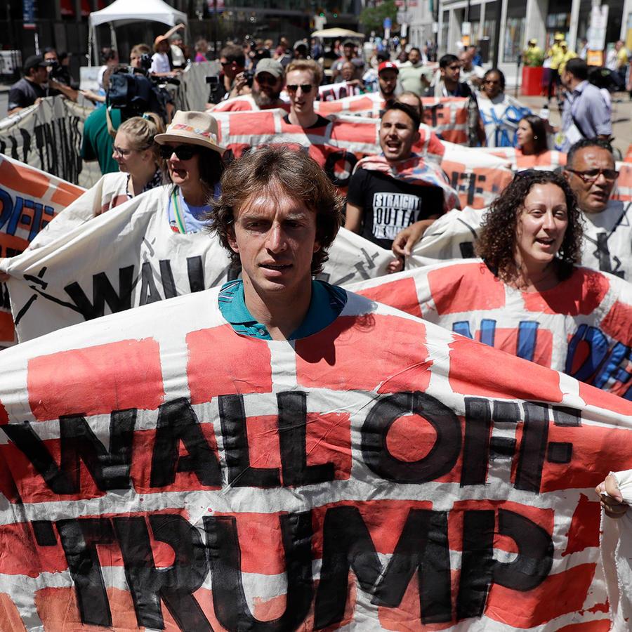 Activistas a favor de los derechos de los inmigrantes sostienen una lona que simboliza un muro en rechazo a la política migratoria de Donald Trump frente al estadio donde se celebra la convención republicana, el miércoles 20 de julio de 2016 en Cleveland