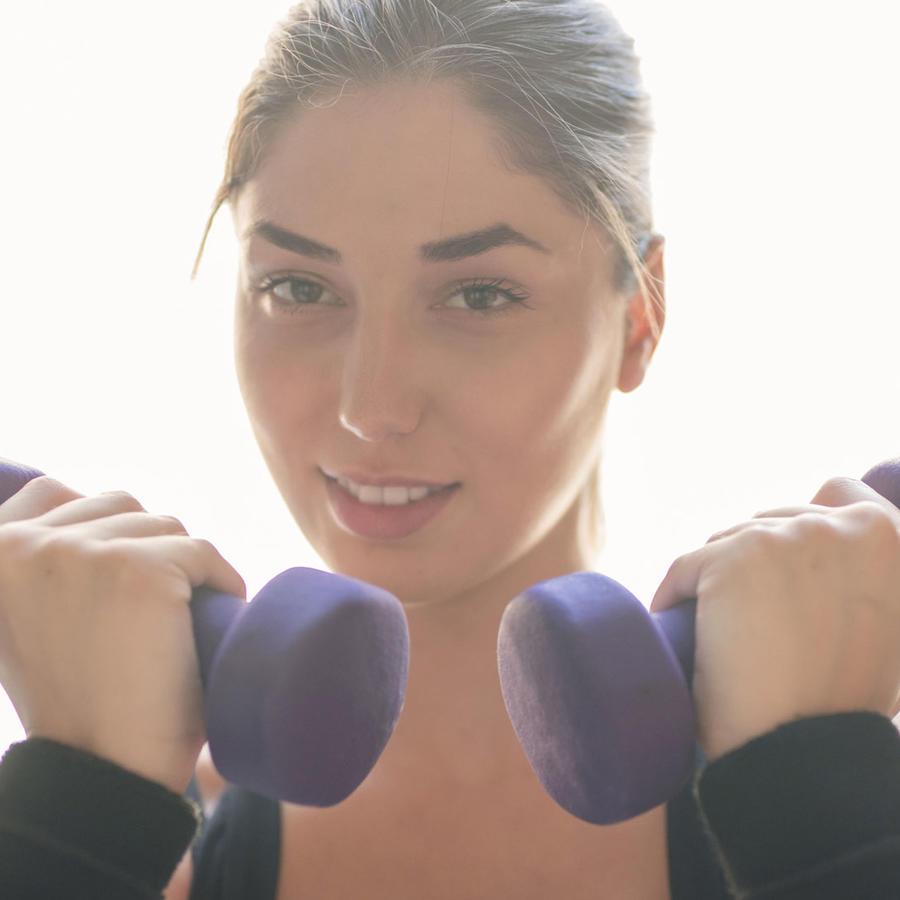 Mujer joven ejercitándose con pesas ligeras