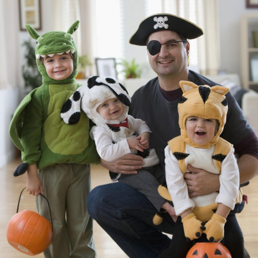 Padre e hijos pequeños listos para festejar Halloween