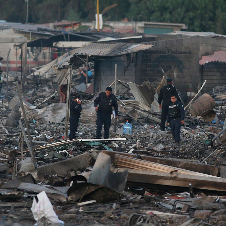 Policías caminan sobre lo que quedó del mercado San Pablito en Tultepec, México tras una explosión el martes 20 de diciembre del 2016