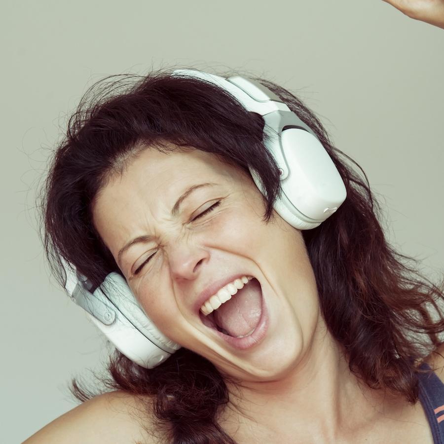 Mujer joven cantando con auriculares