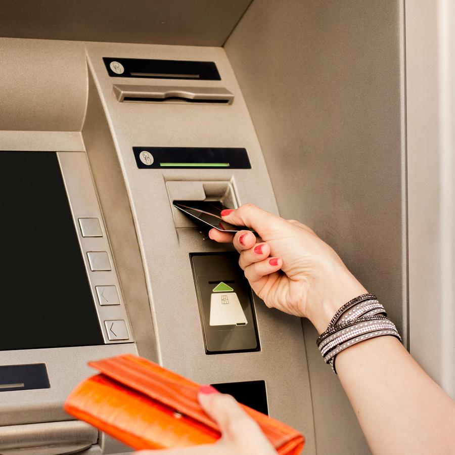 Mujer joven retira dinero de un ATM