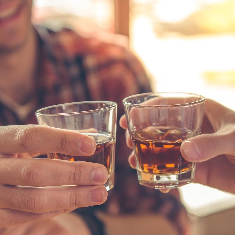 Hombre bebiendo un shot de alcohol