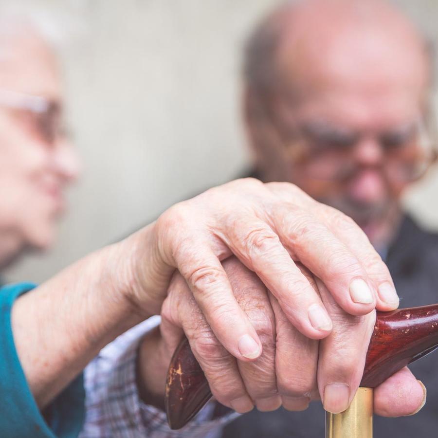 Una pareja de ancianos se dan la mano.