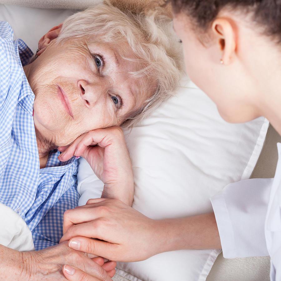 Cuidando a una mujer mayor enferma en la cama