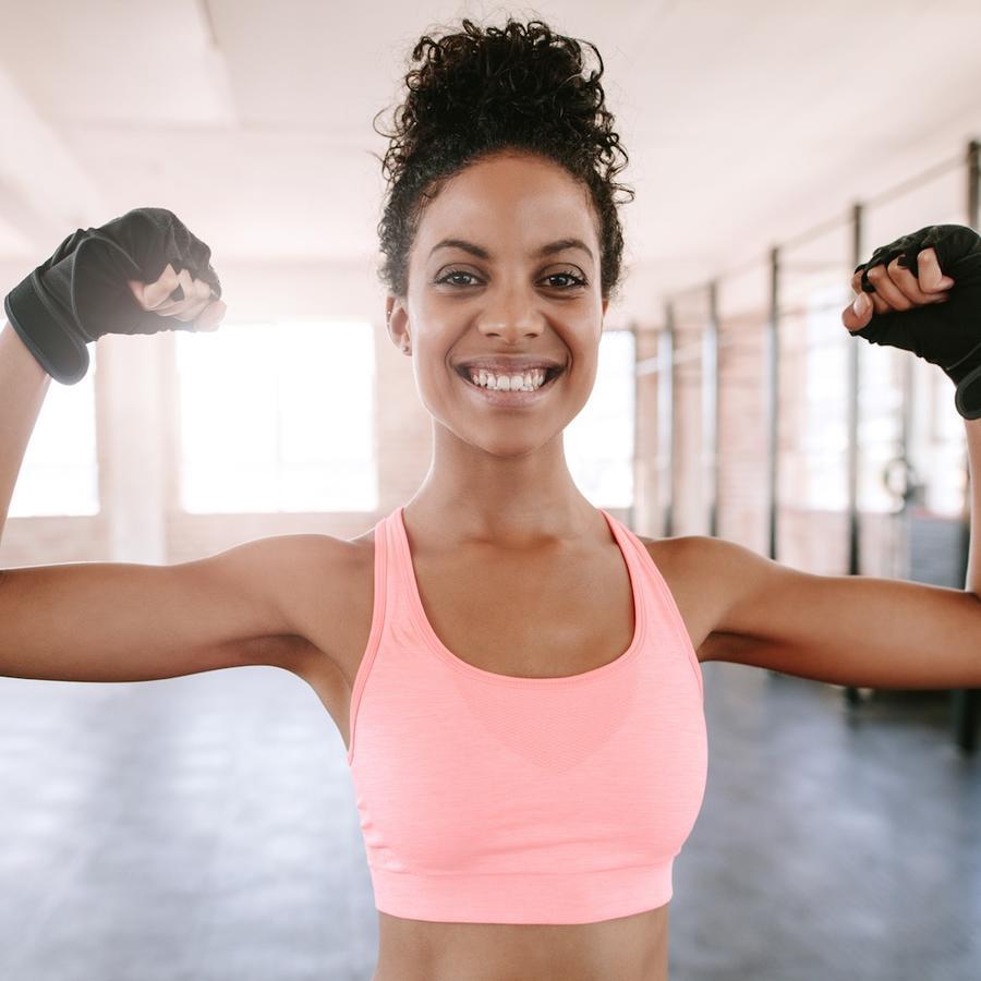 Mujer en el gimnasio con los brazos levantados