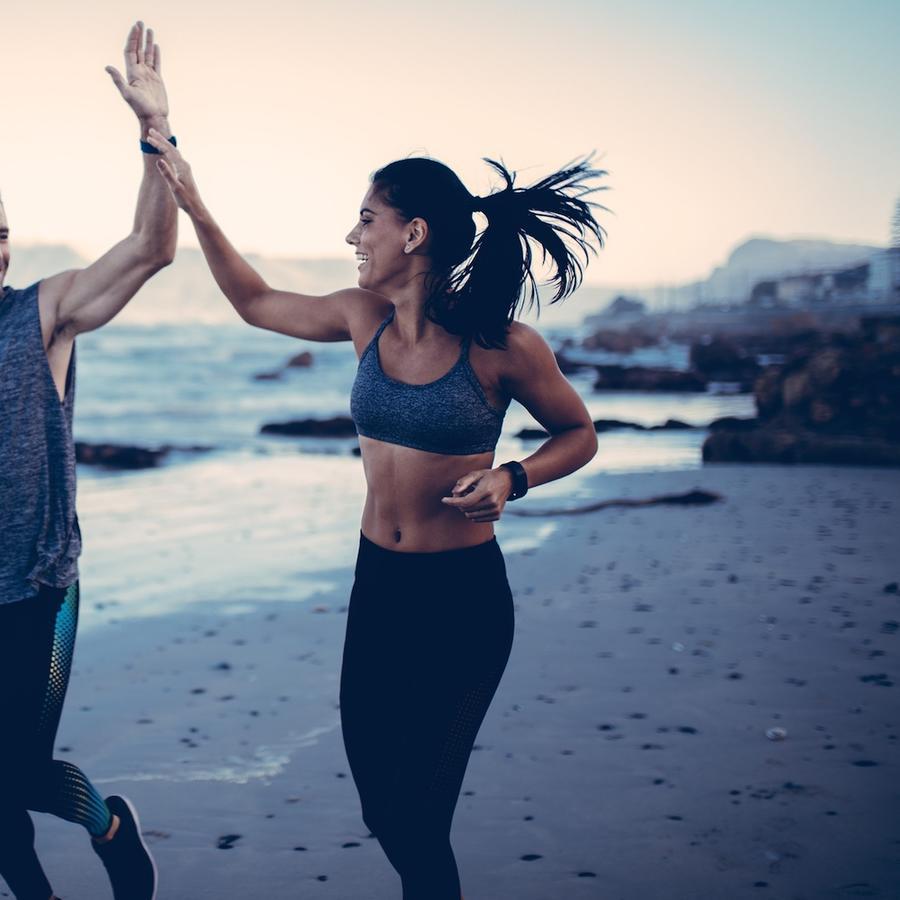 Hombre y mujer haciendo ejercicio en la playa