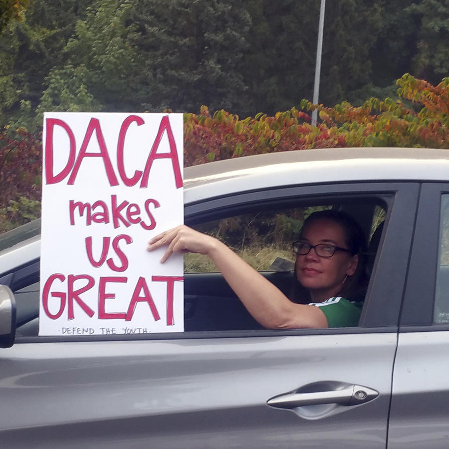 Una persona conduce en un vehículo con un cartel de apoyo a DACA