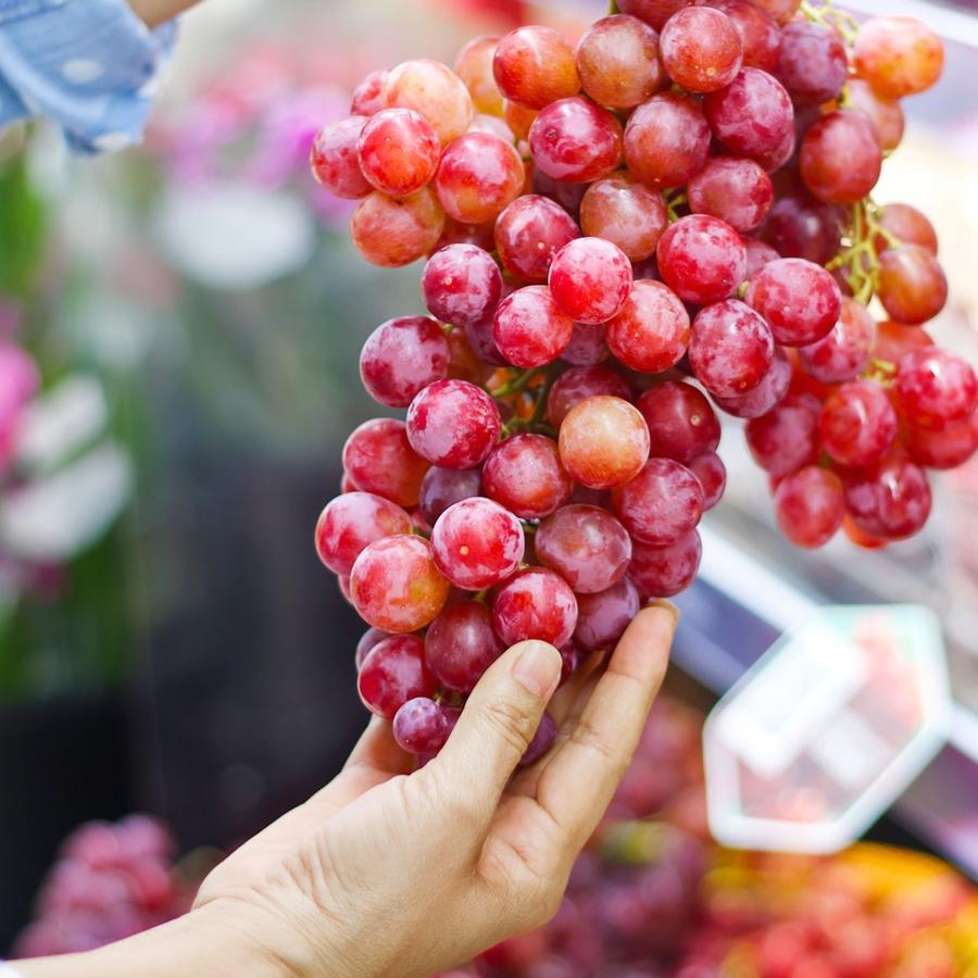 Persona comprando uvas en la tienda