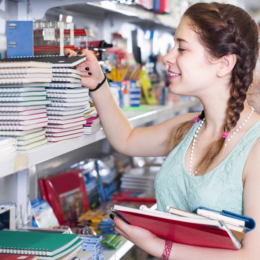 Chica eligiendo cuadernos en una tienda