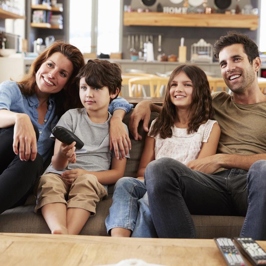 Familia en su sofá viendo una película
