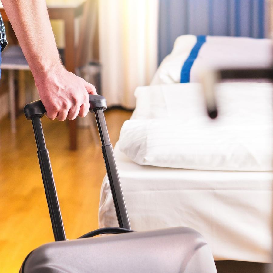 Persona con valija entrando a habitación