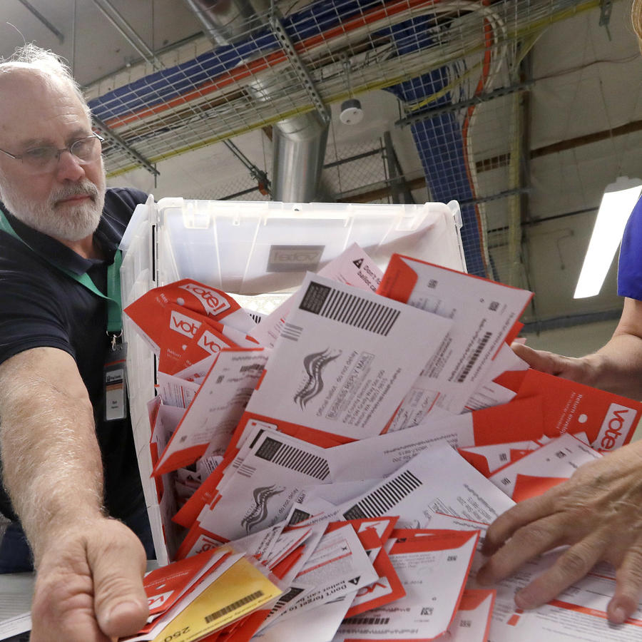 Los trabajadores depositan las boletas electorales que dejaron en un buzón para clasificarlas