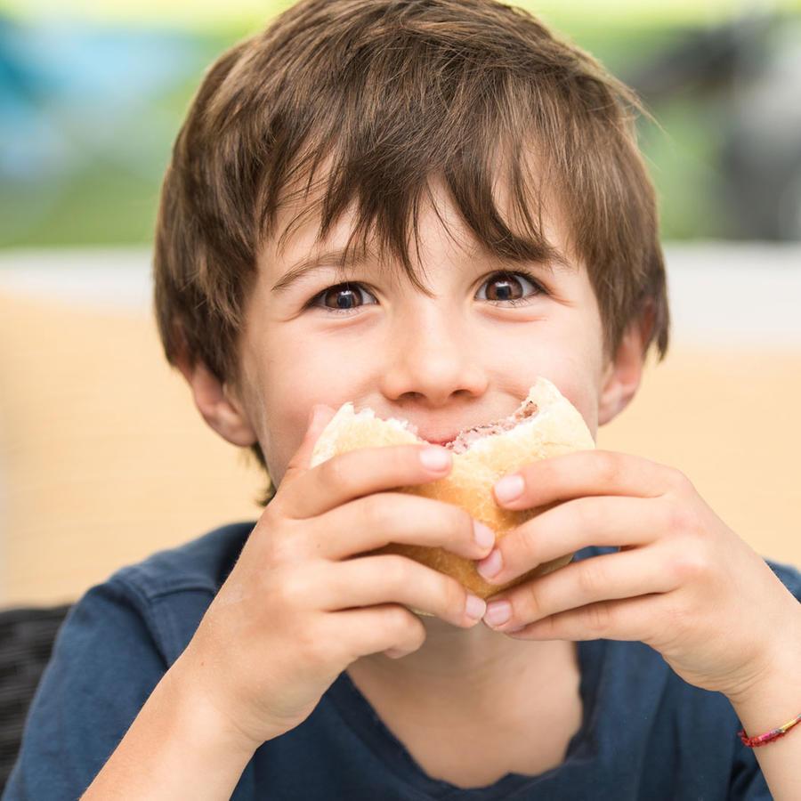 Niño comiendo una hamburguesa