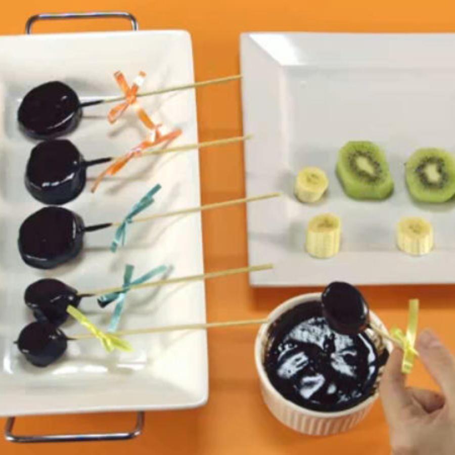 Plato de frutas cubiertas en chocolate derretido