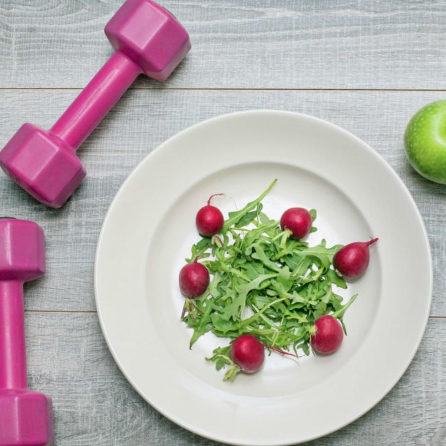 Plato de ensalada sobre una mesa, junto a un par de pesas rosas