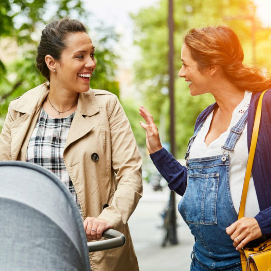 Mujer embarazada y mujer con carriola caminando