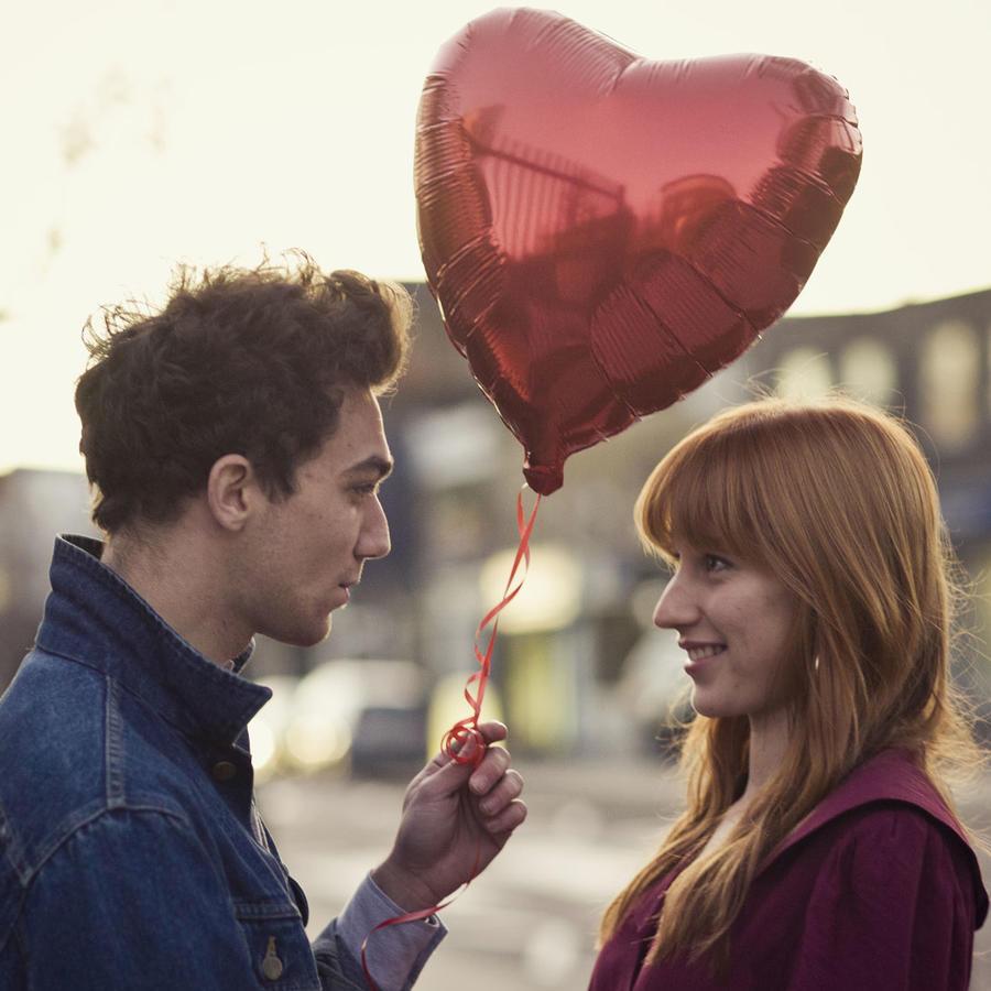 Pareja sosteniendo un globo en forma de corazón