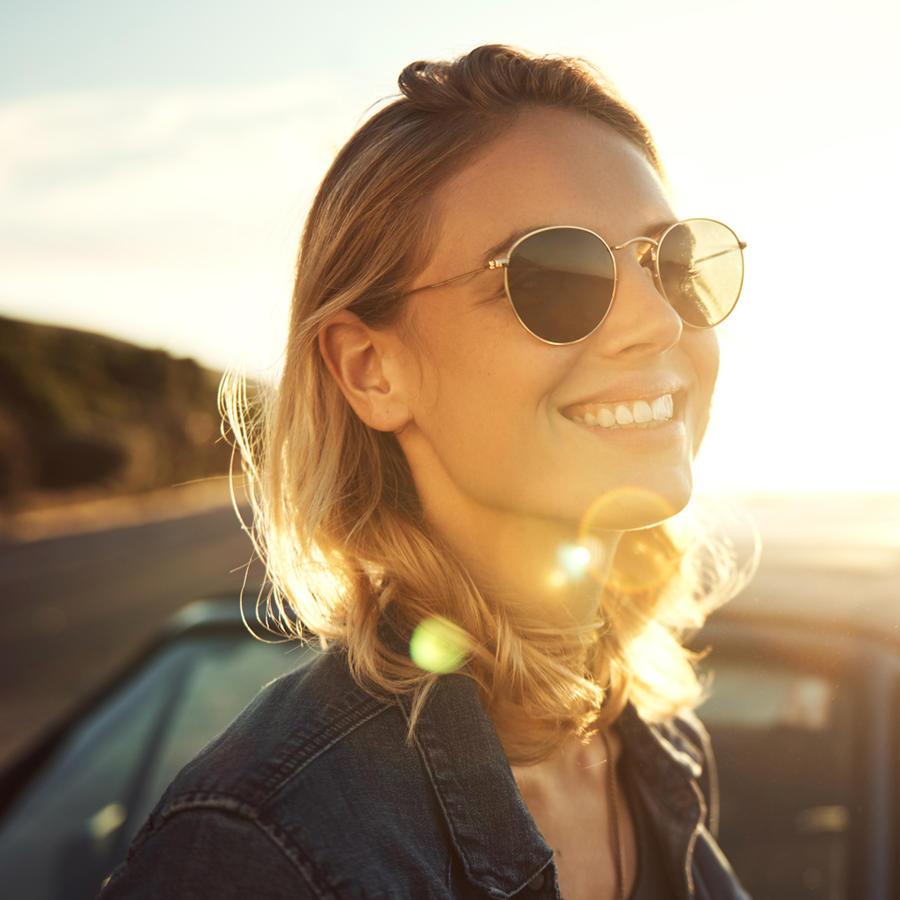 Mujer sonriendo frente al atardecer
