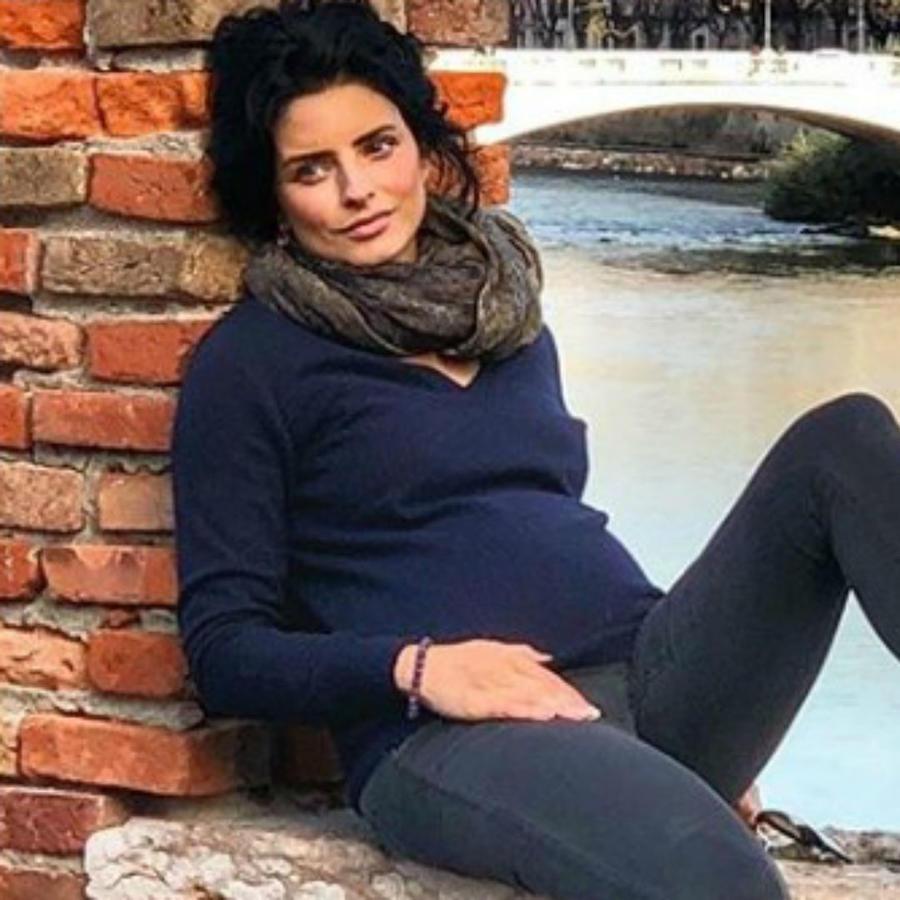Aislinn Derbez sentada en una ventana