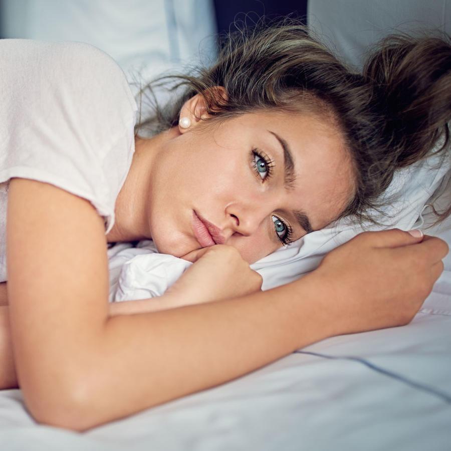 Mujer joven acostada en la cama