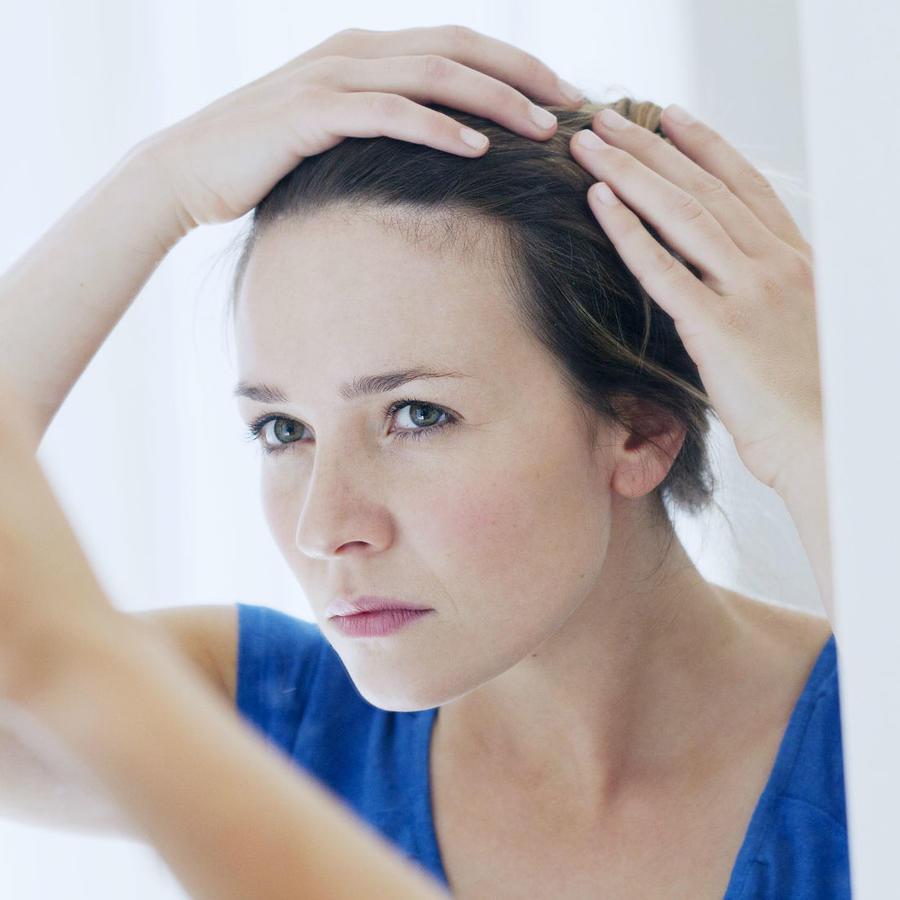 Mujer mirando su cabello grasoso en el espejo