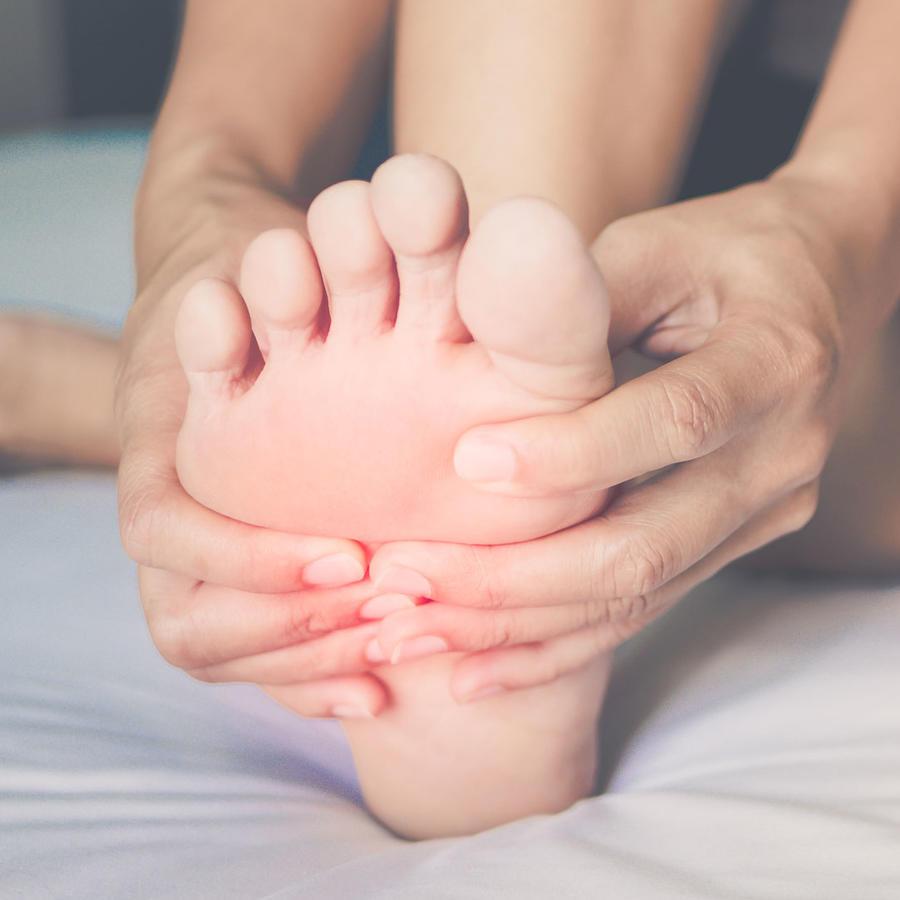 Mujer tocando su pie