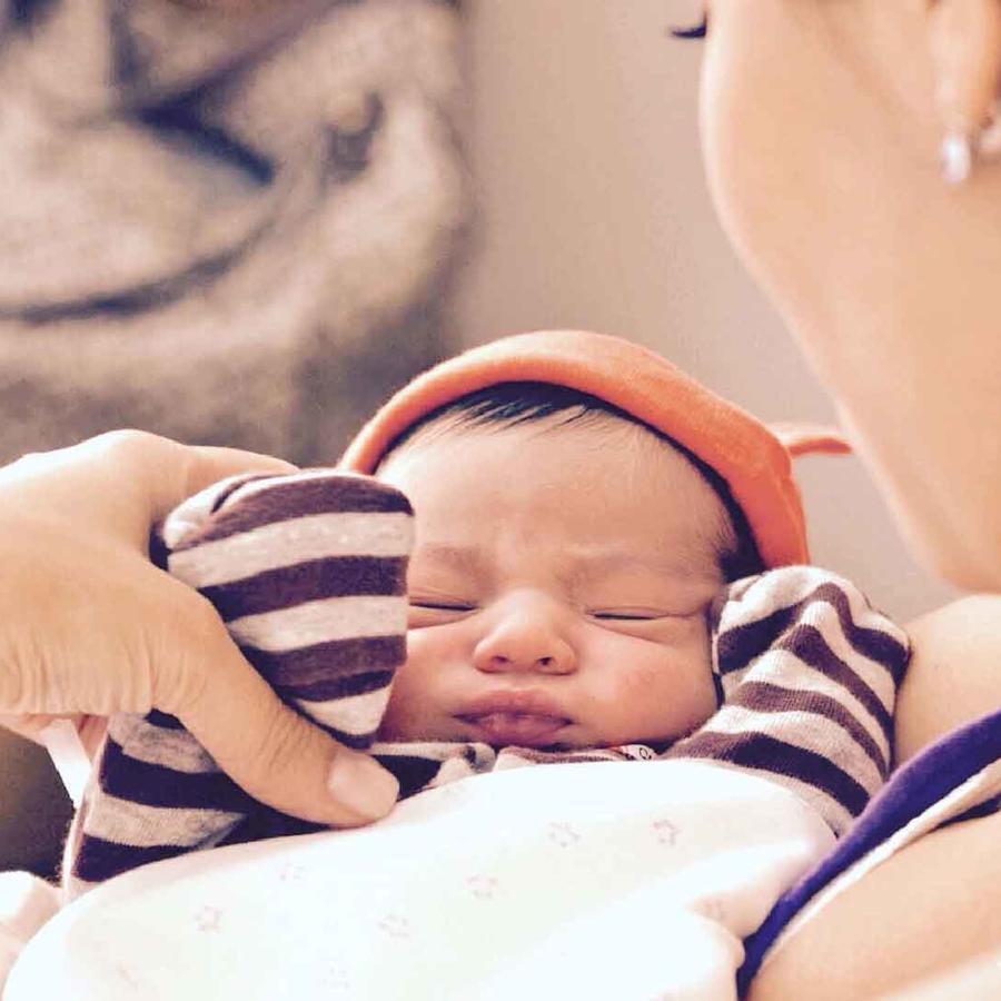 Mamá carga a su bebé recién nacido