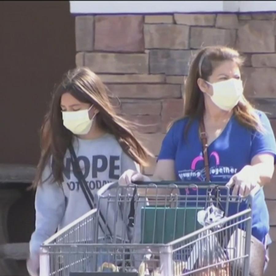 Madre hija salen de hacer sus compras con mascarilla