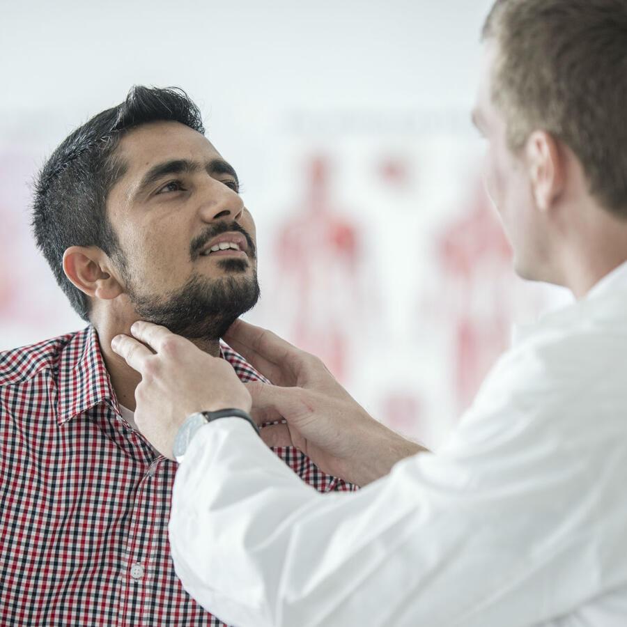 Doctor revisando la garganta de su paciente