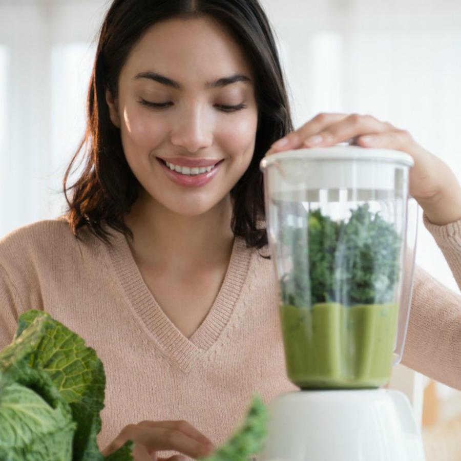 Mujer preparando un jugo verde