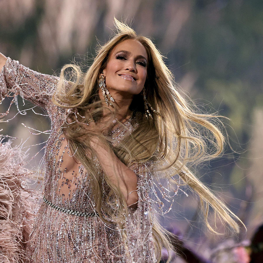 Jennifer Lopez en escenario sonriendo.