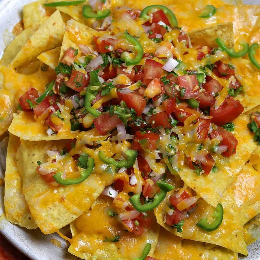 nachos en un plato con dips, ajo y cebolla