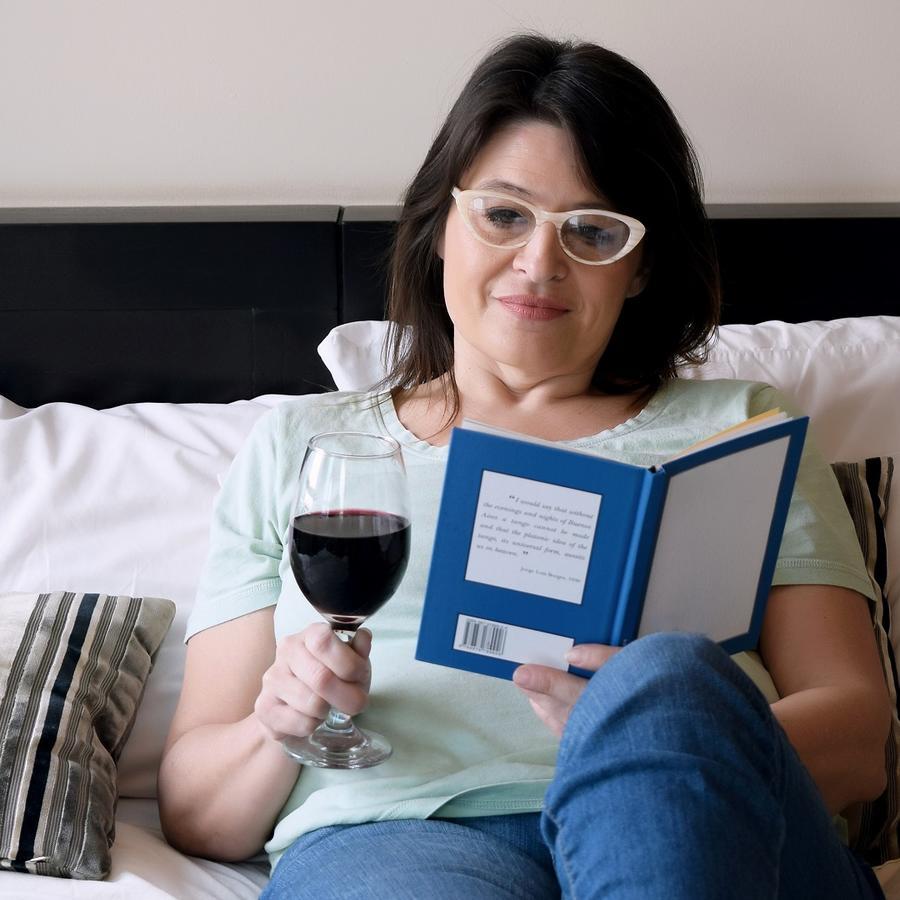 Mujer recostada en la cama leyendo y bebiendo vino tinto