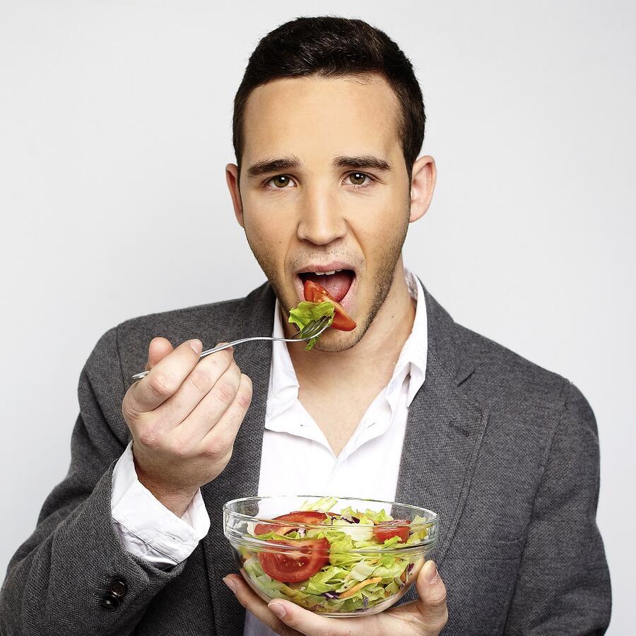 Hombre con saco gris comiendo una ensalada