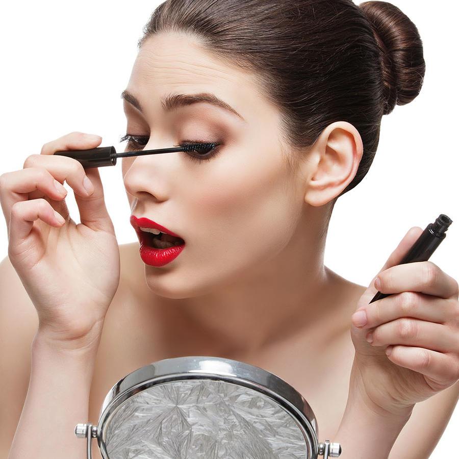 Mujer aplicándose rímel frente a un espejo pequeño