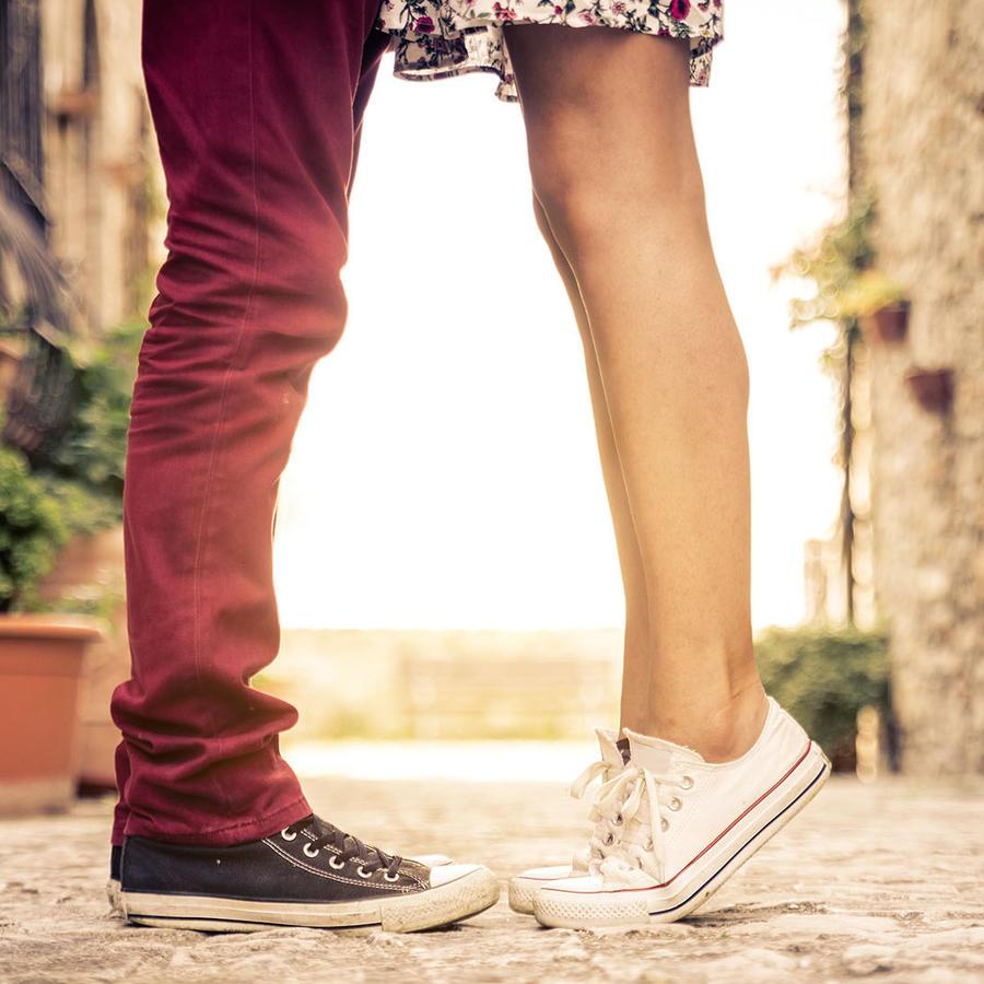 Mujer en puntitas de pie junto a un hombre