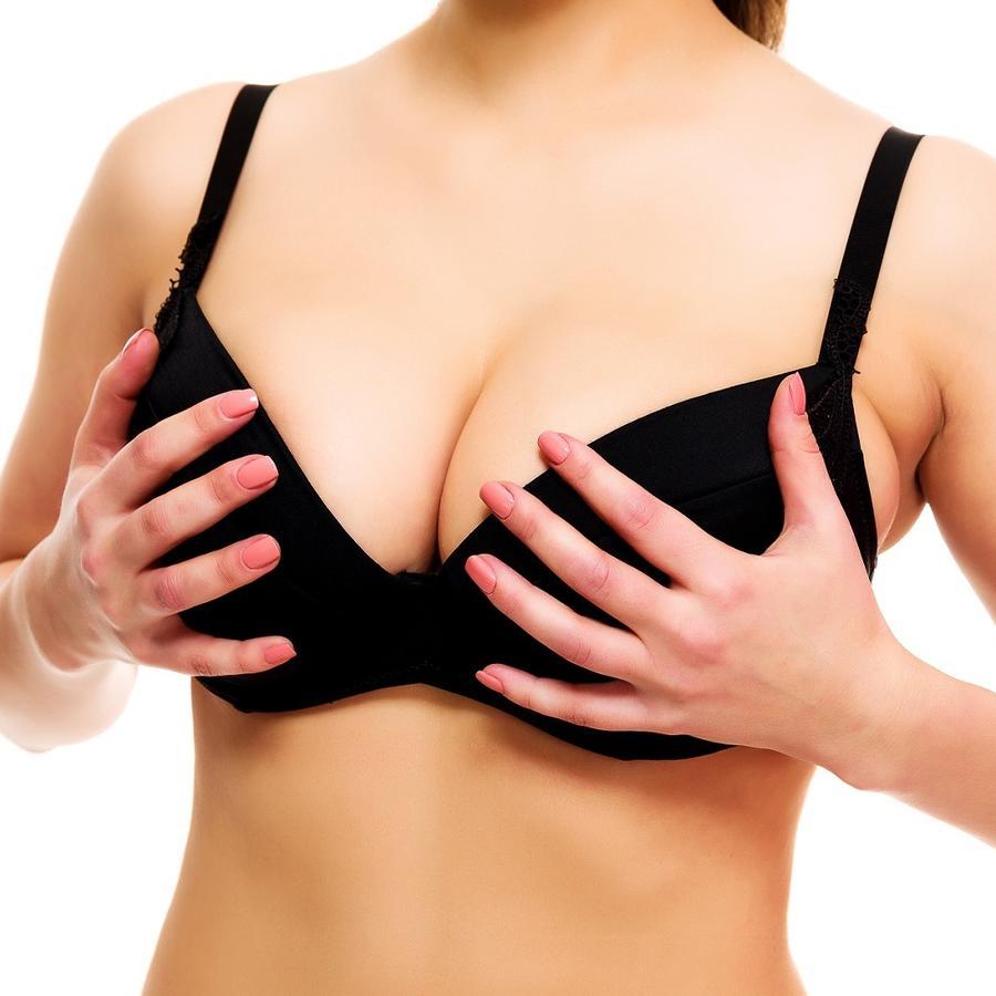 Mujer con bra negro sosteniéndose los pechos con las manos