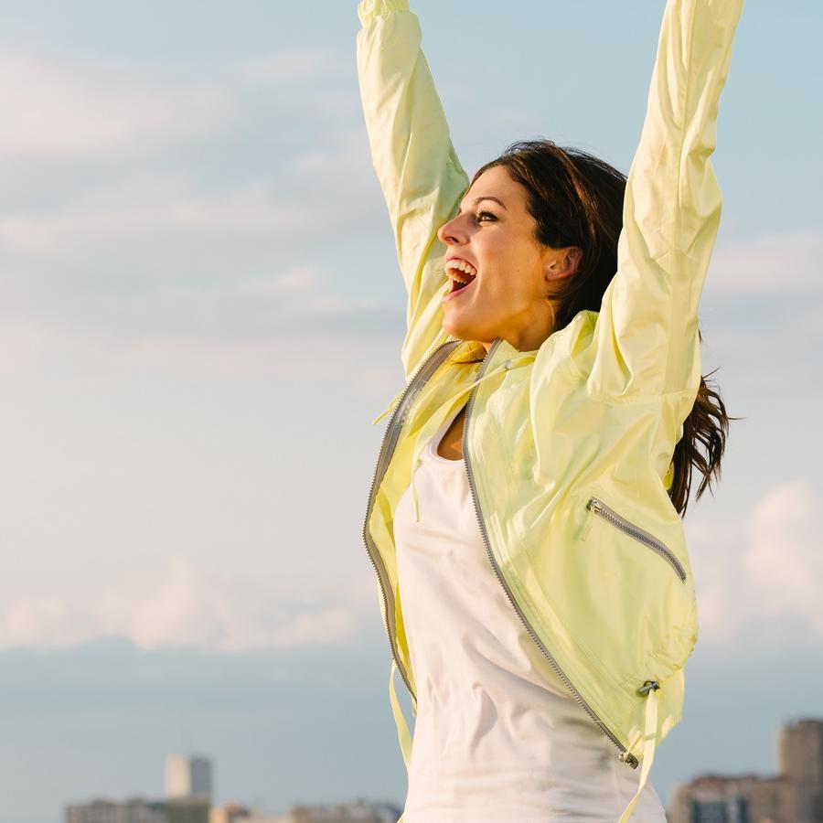 Mujer con blusa blanca y amarilla abriendo los brazos contenta