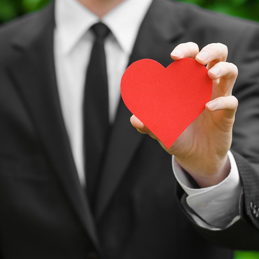 hombre de traje sosteniendo un corazón