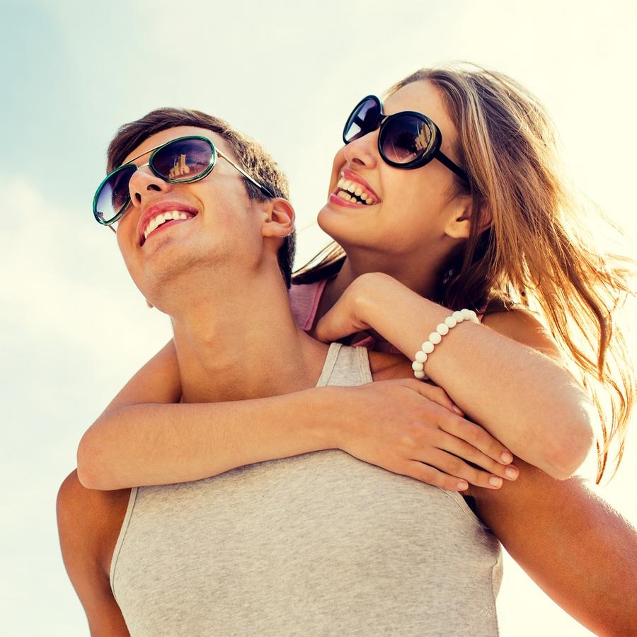 Mujer con lentes oscuros abrazando a un hombre por detrás