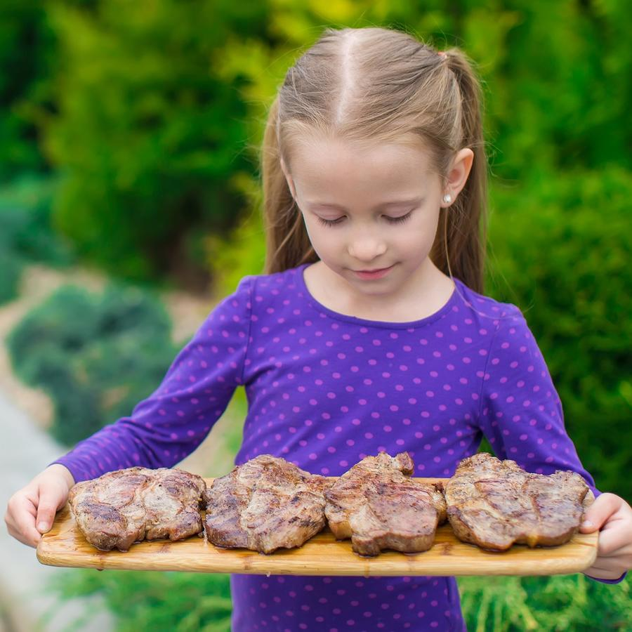 Niña con blusa morada sosteniendo una tabla con trozos de carne
